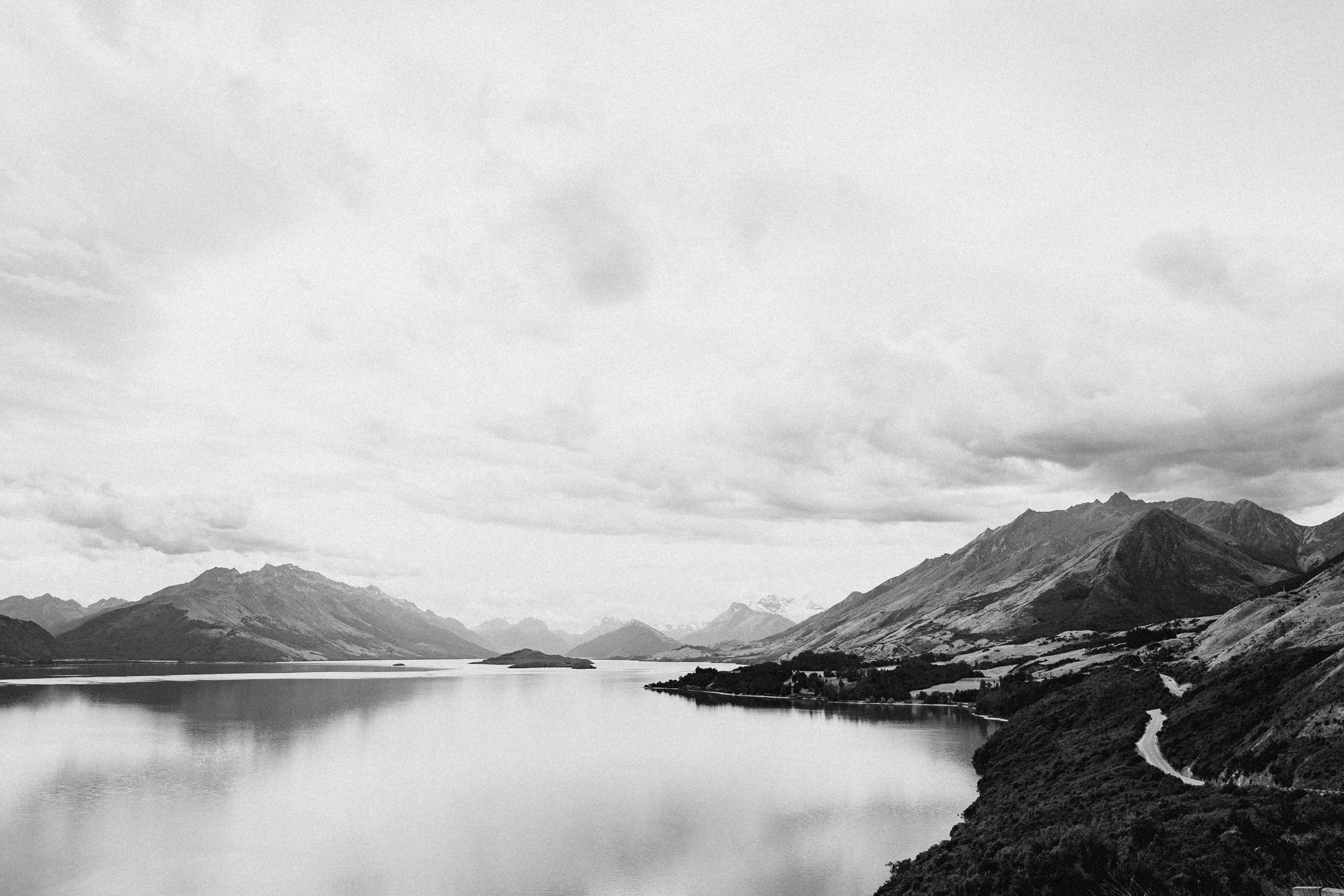grayscale landscape photography of a lake near mountains
