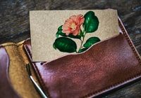 orange petaled flower-printed card in opened brown leather bifold wallet