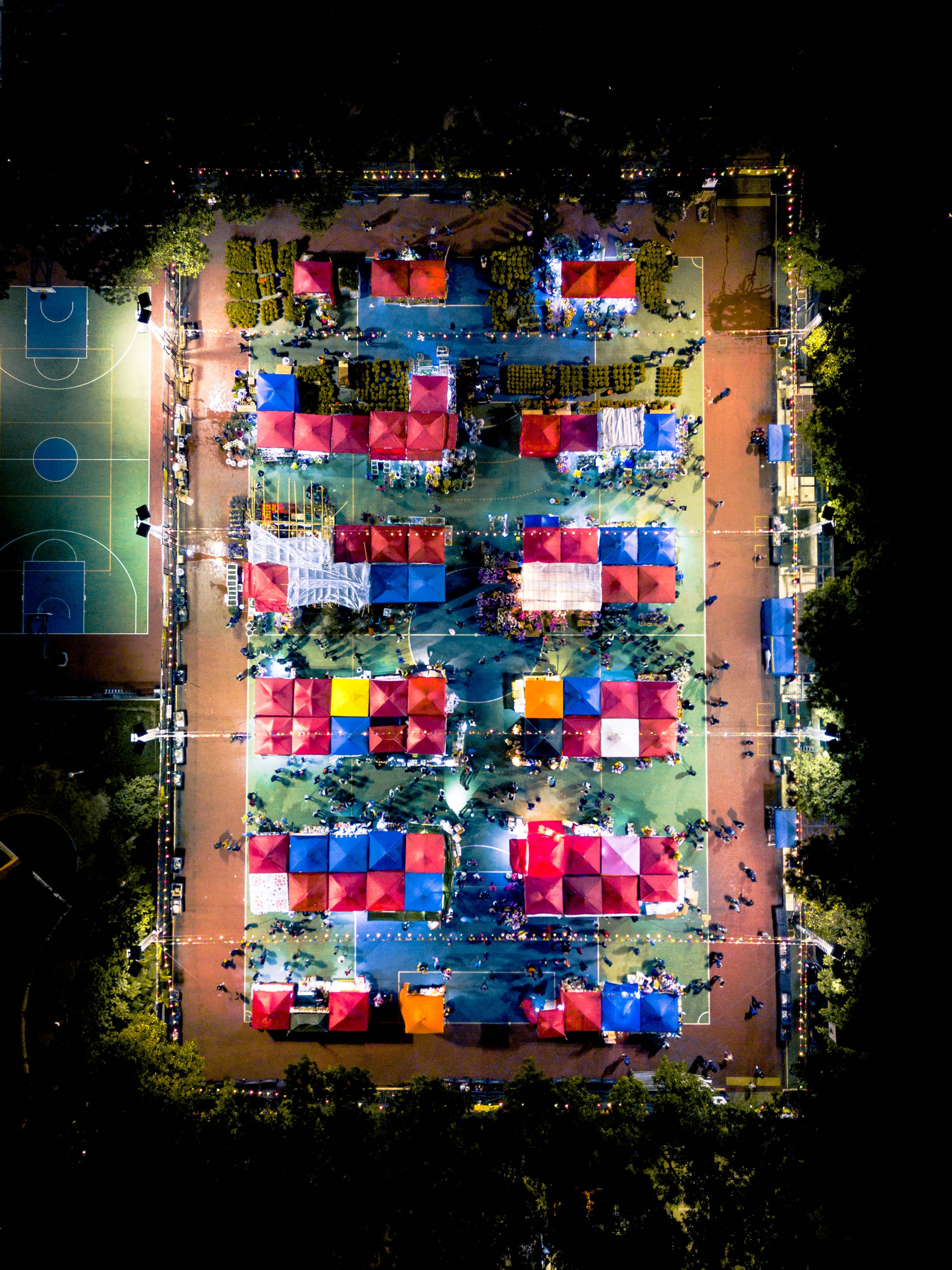 aerial photography of field with parasols near basketball court at daytime