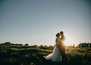 bride and groom on green grass field