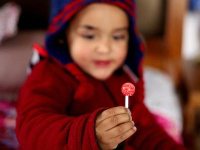 baby holding lollipop sweet teams background