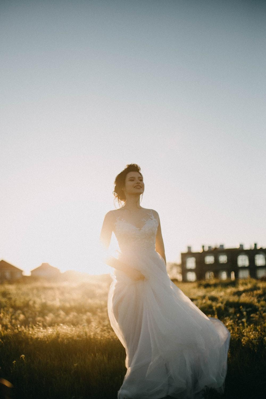 woman in white spaghetti strap dress smiling during daytime