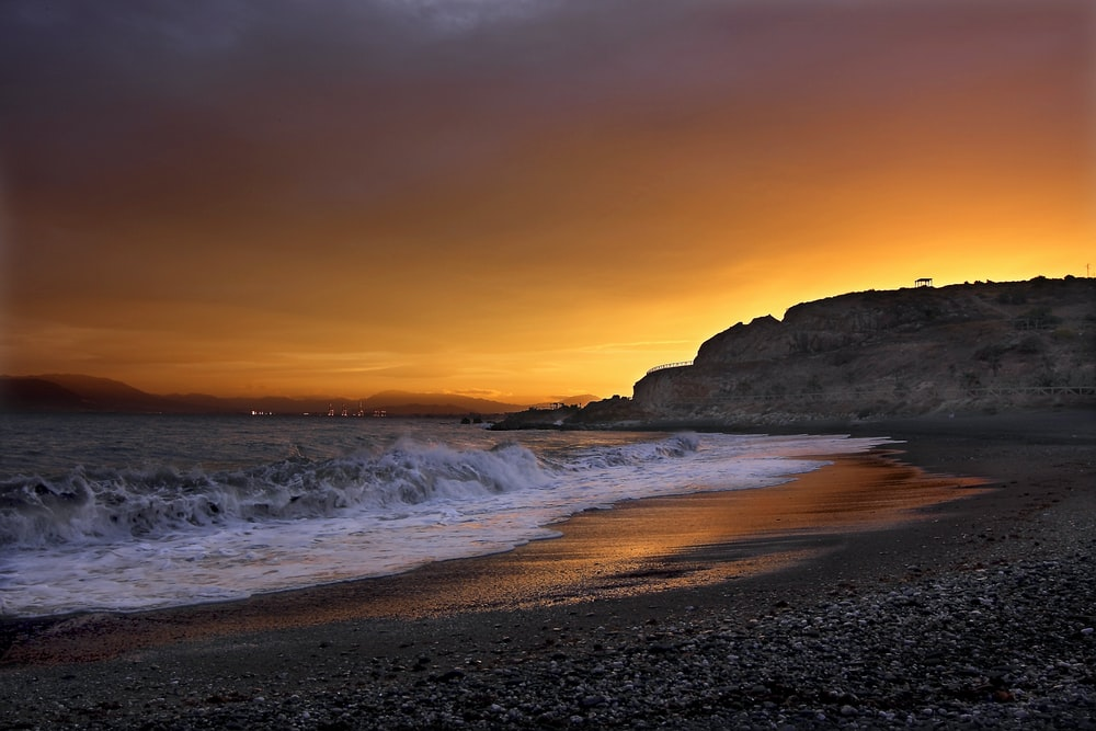 landscape photography of seashore near cliff