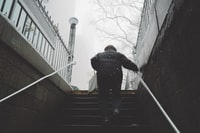 person walking on stairway holding on railings under cloudy sky