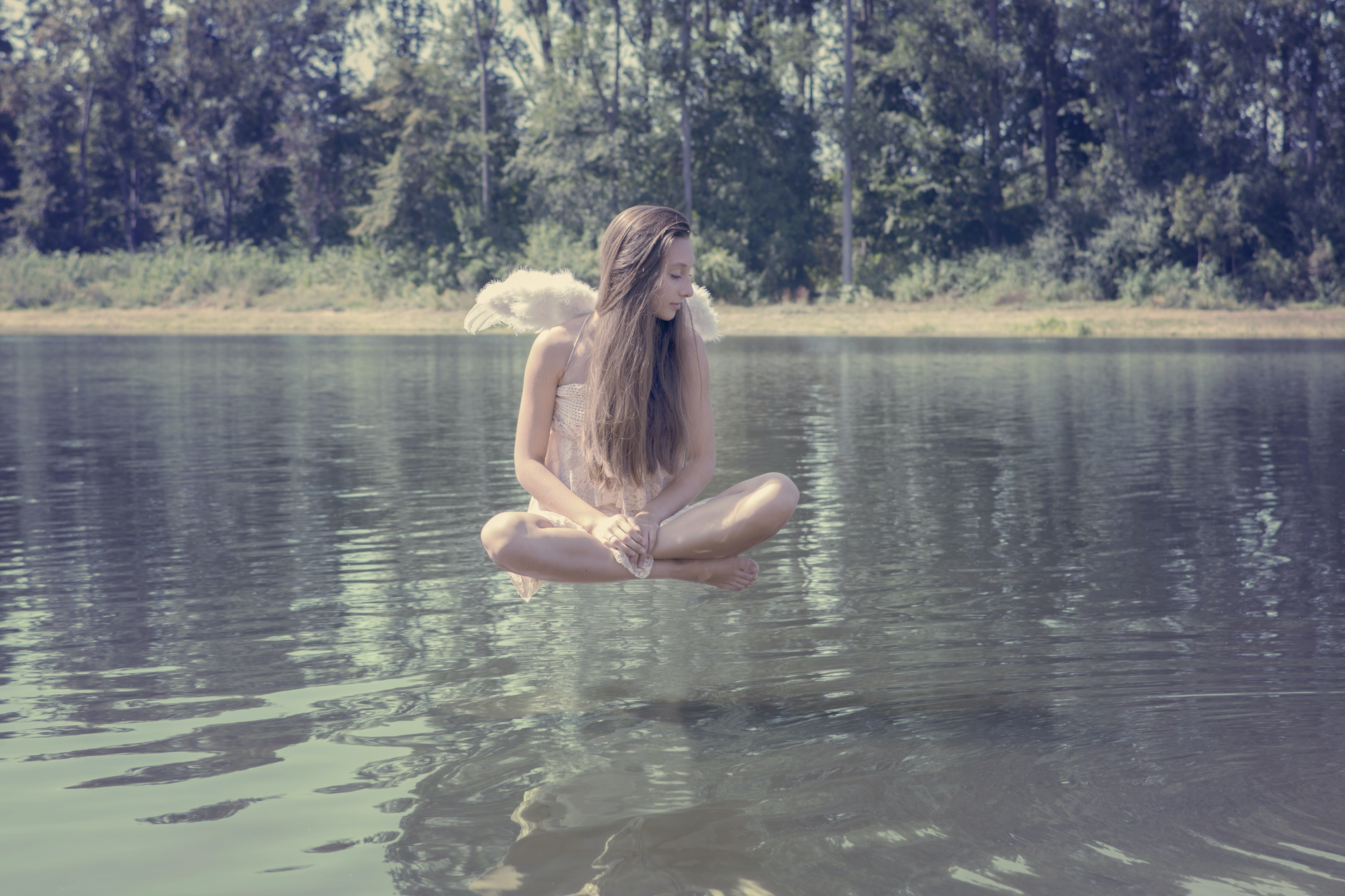 woman floating above body of water