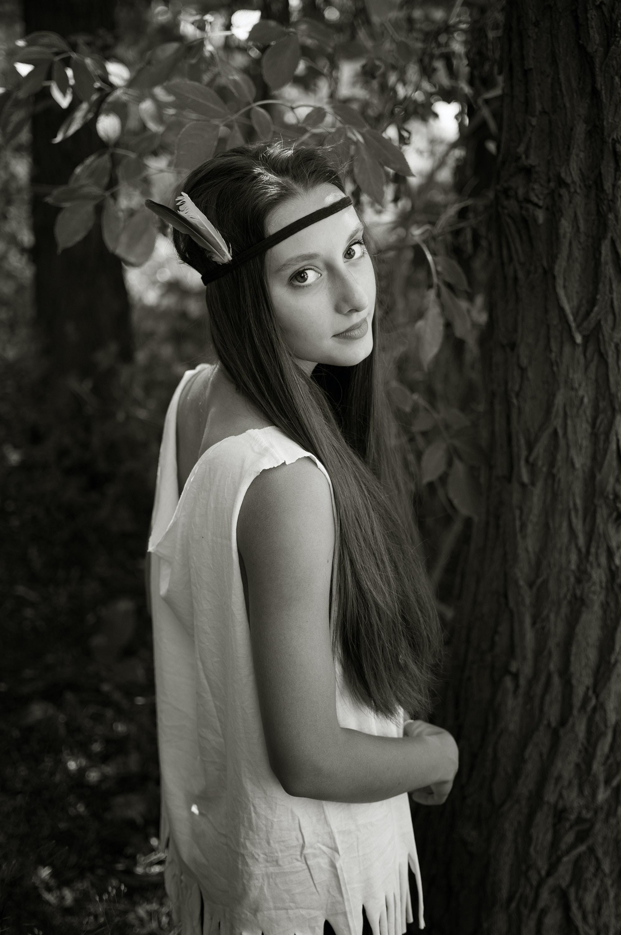 grayscale photo of woman near tree