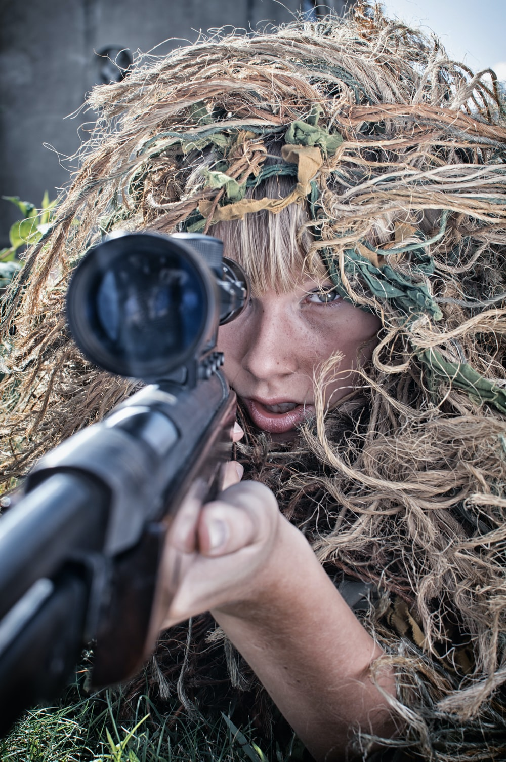 woman wearing gillie suit holding sniper rifle