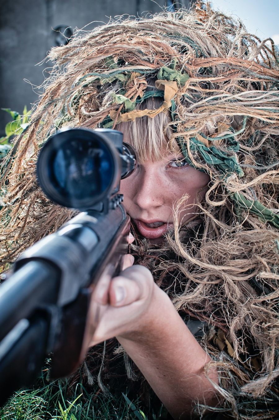 A woman in camouflage points a sniper rifle at a location off-camera.