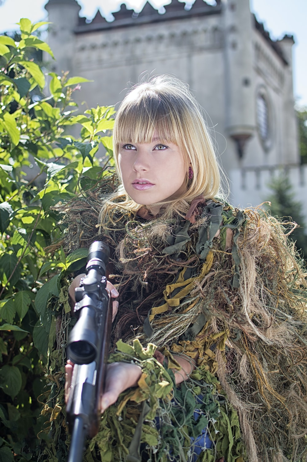 woman covered with grass while holding sniper rifle
