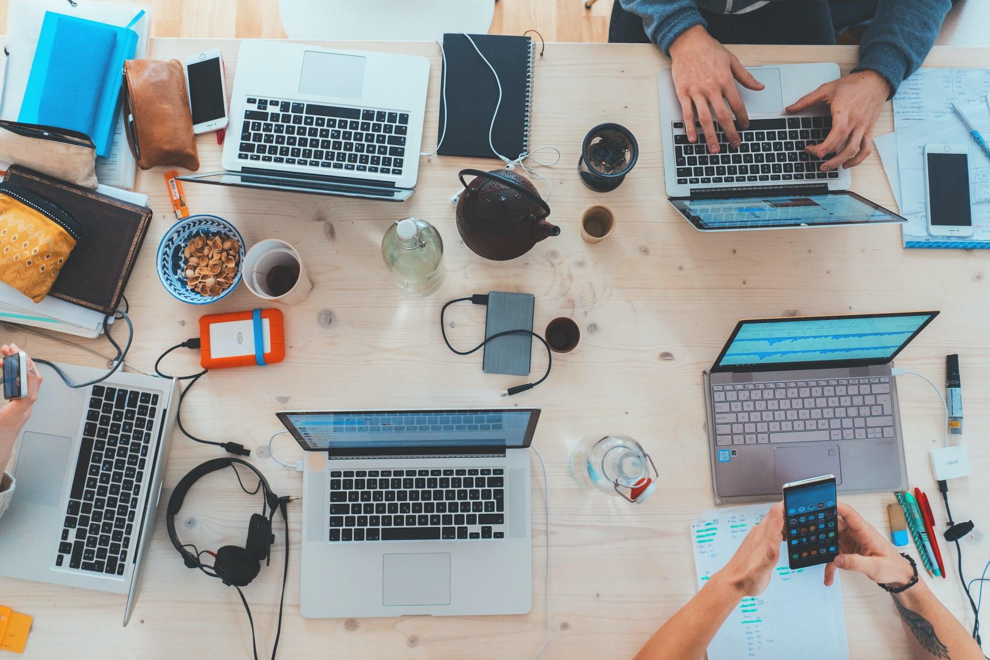 Essência do DataOps: pessoas trabalhando juntas, em sistemas colaborativos. Na imagem tem cinco notebooks, alguns fones de ouvido, canetas, copos de café e mãos manuseando esses objetos.