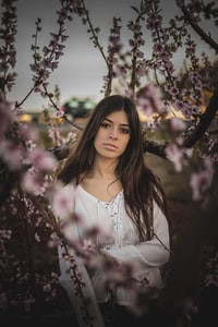 woman in white long-sleeved shirt beneath pink flowers