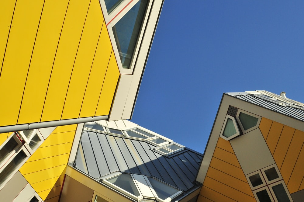 multicolored asymmetrical house architectural low-angle photography under blue sky