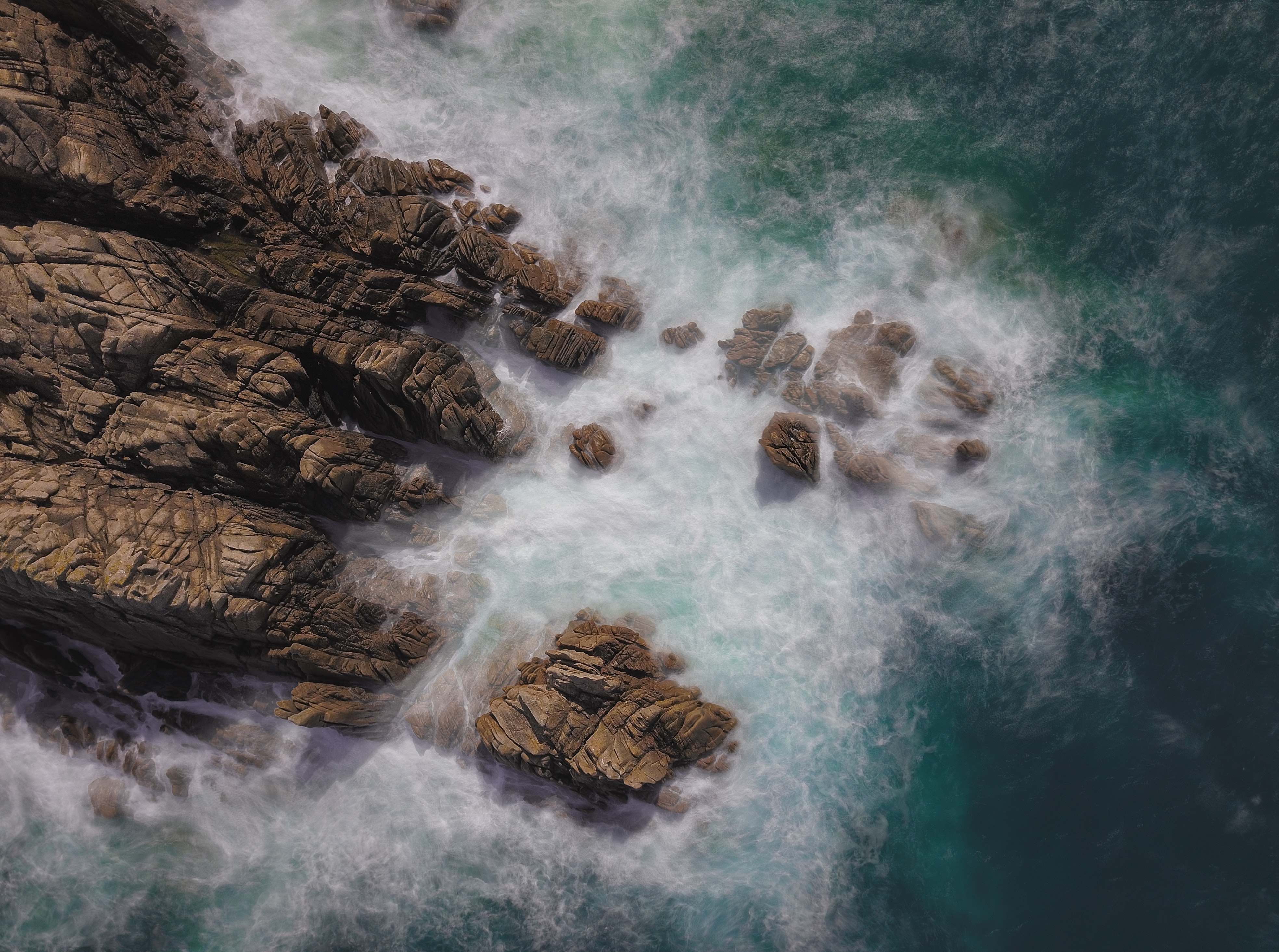 brown rock formation on sea aerial photography