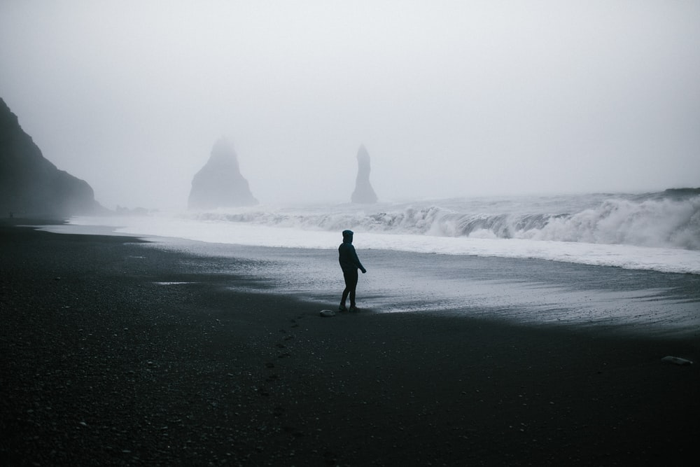 silhouette of man waking on shore