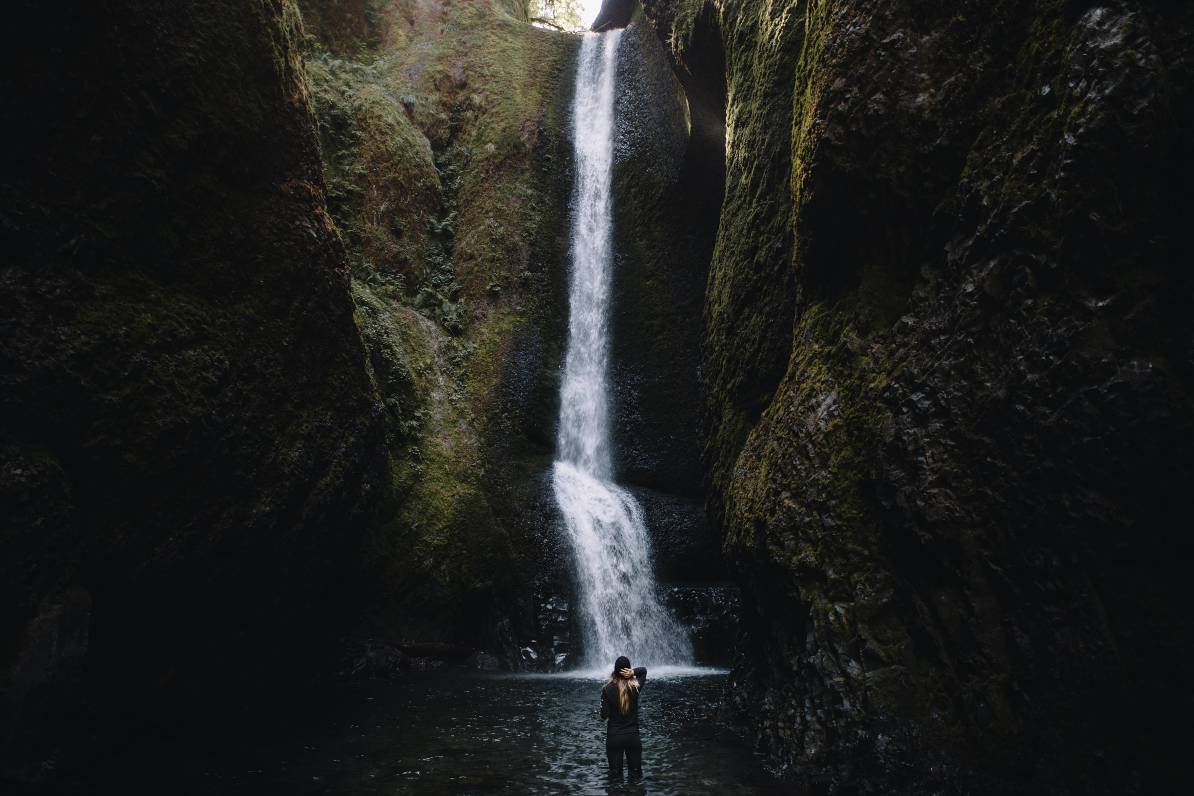 person stands in front of waterfalls during daytime