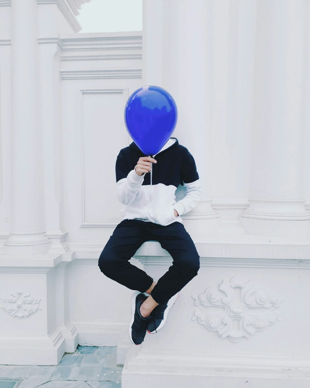 person sitting on white concrete pavement holding blue balloon at daytime