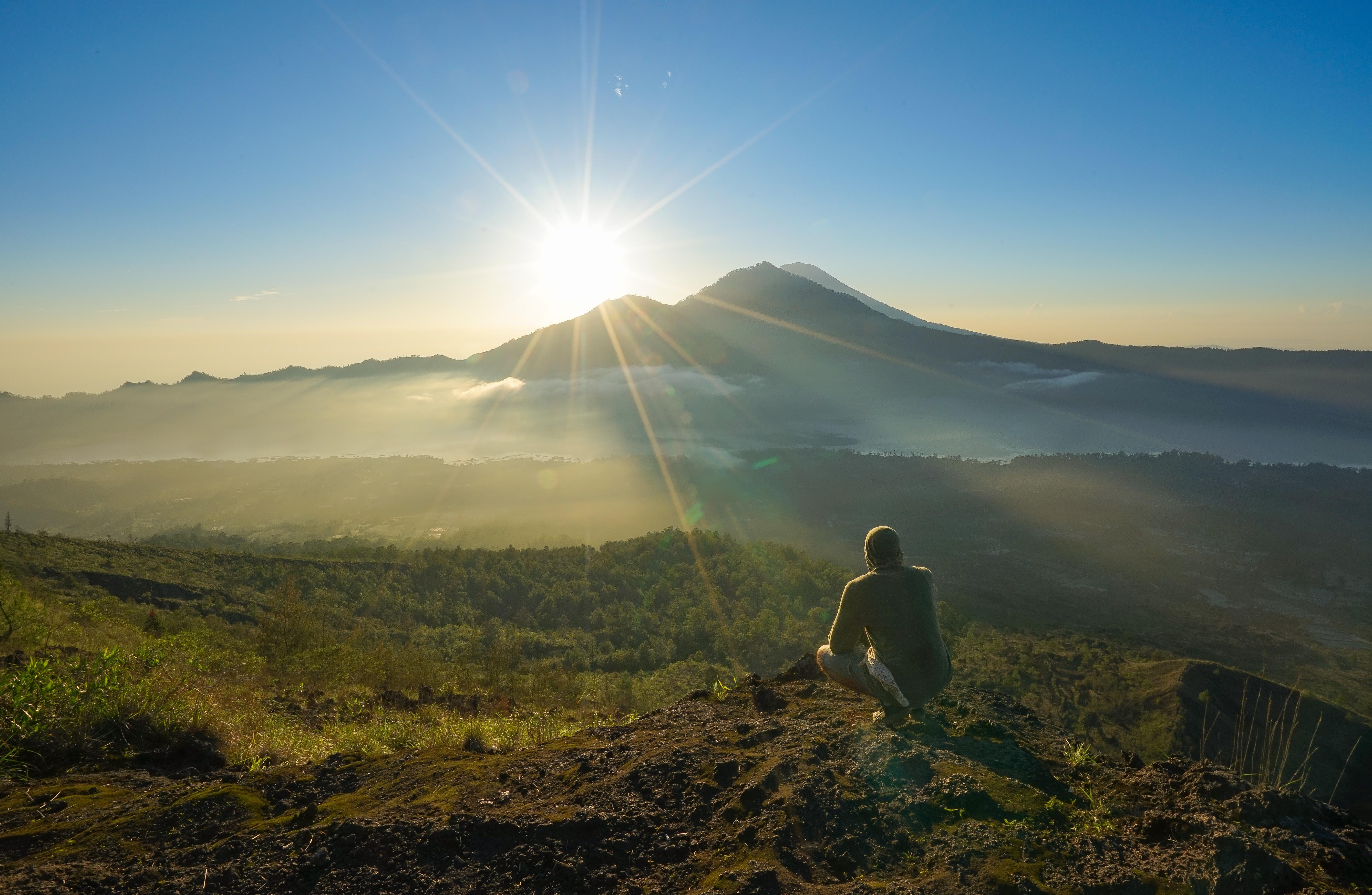 man squatting on mountain top during daytime