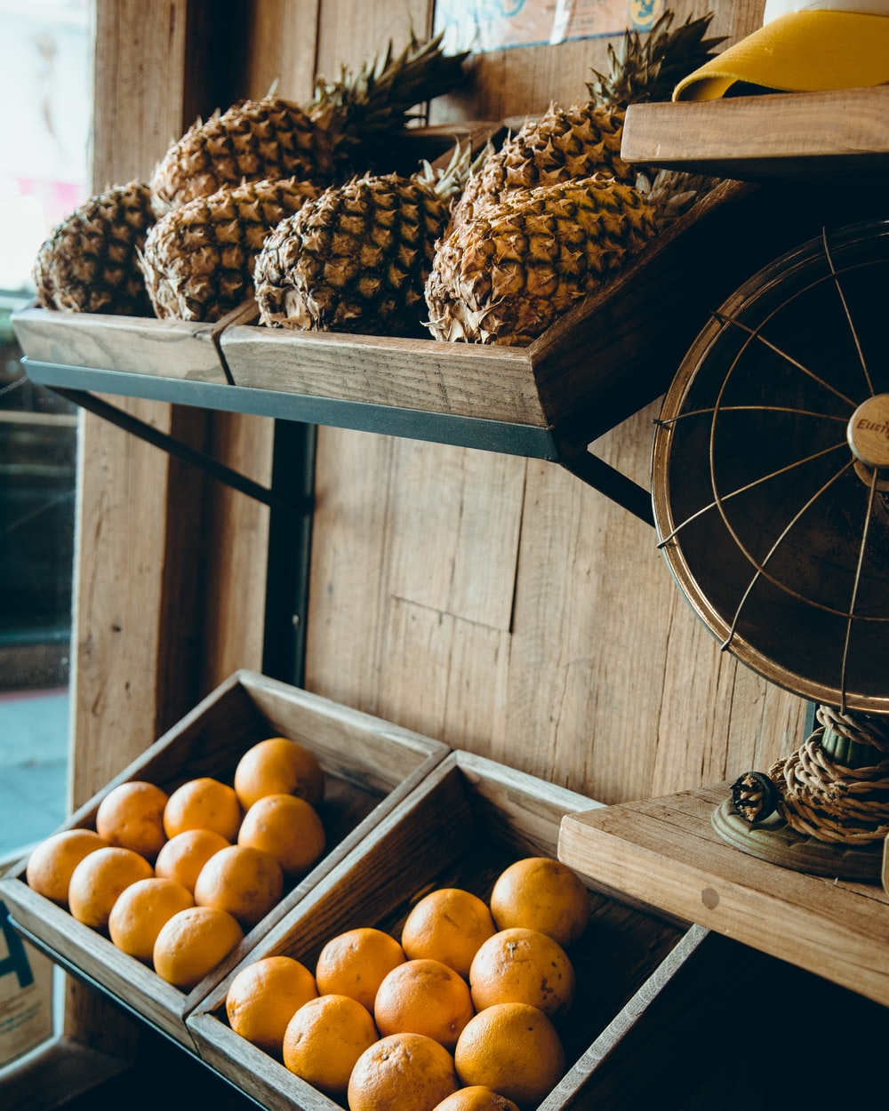 pineapple and orange fruits on brown wooden rack