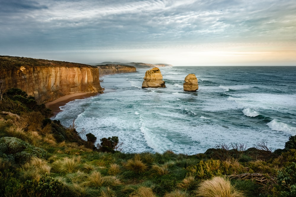 HDR photo of two rock formation on sea under cloudy sky during daytime