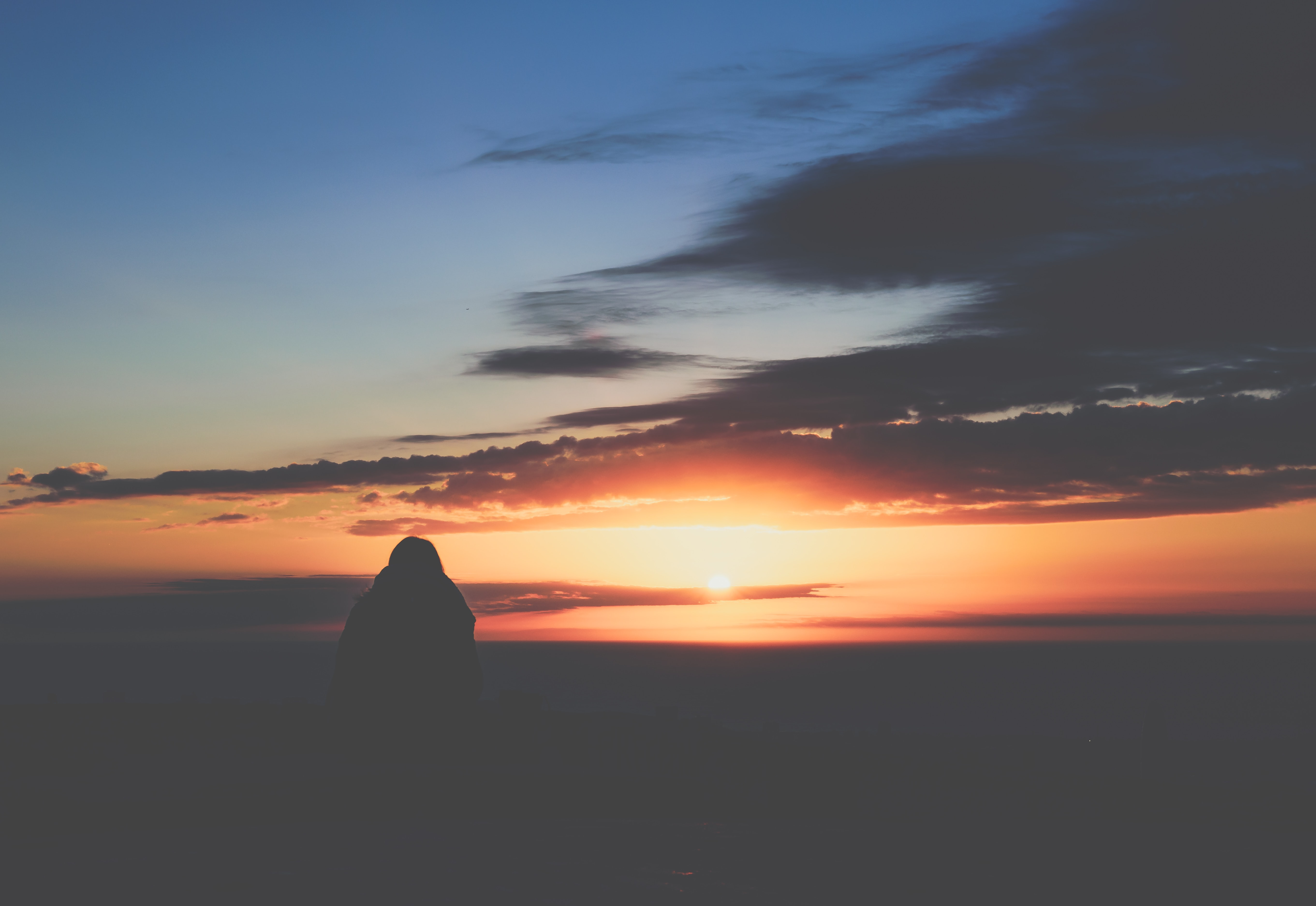 silhouette photo of rock formation during sunset