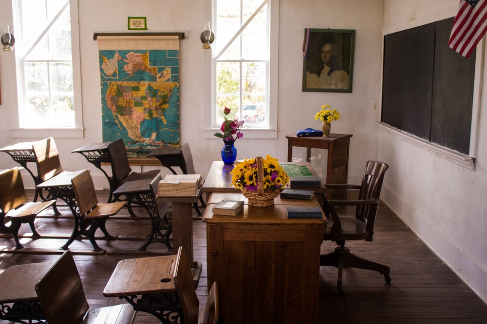 vacant white painted classroom with chairs, tables , and map on the wall