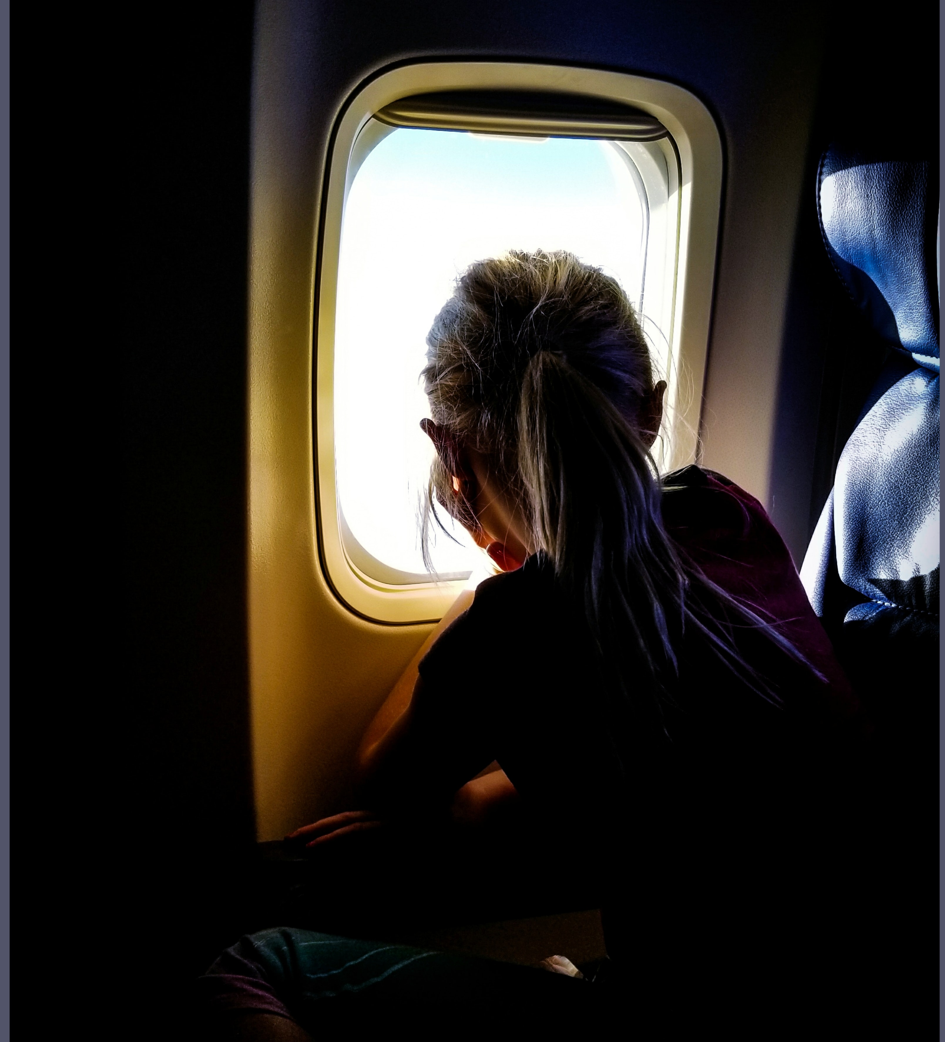 woman sitting on plane while looking at the window