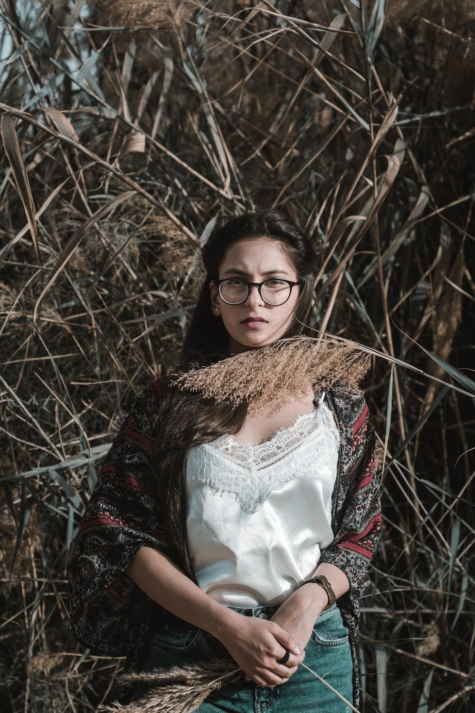 woman standing beside bamboo plants