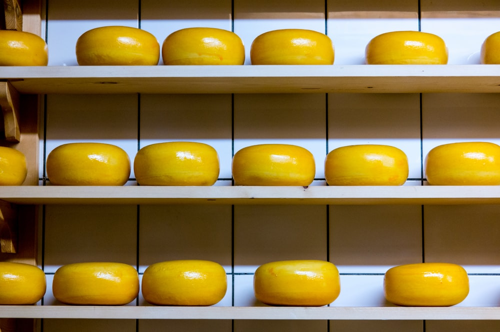 yellow cheese lot on brown wooden shelf
