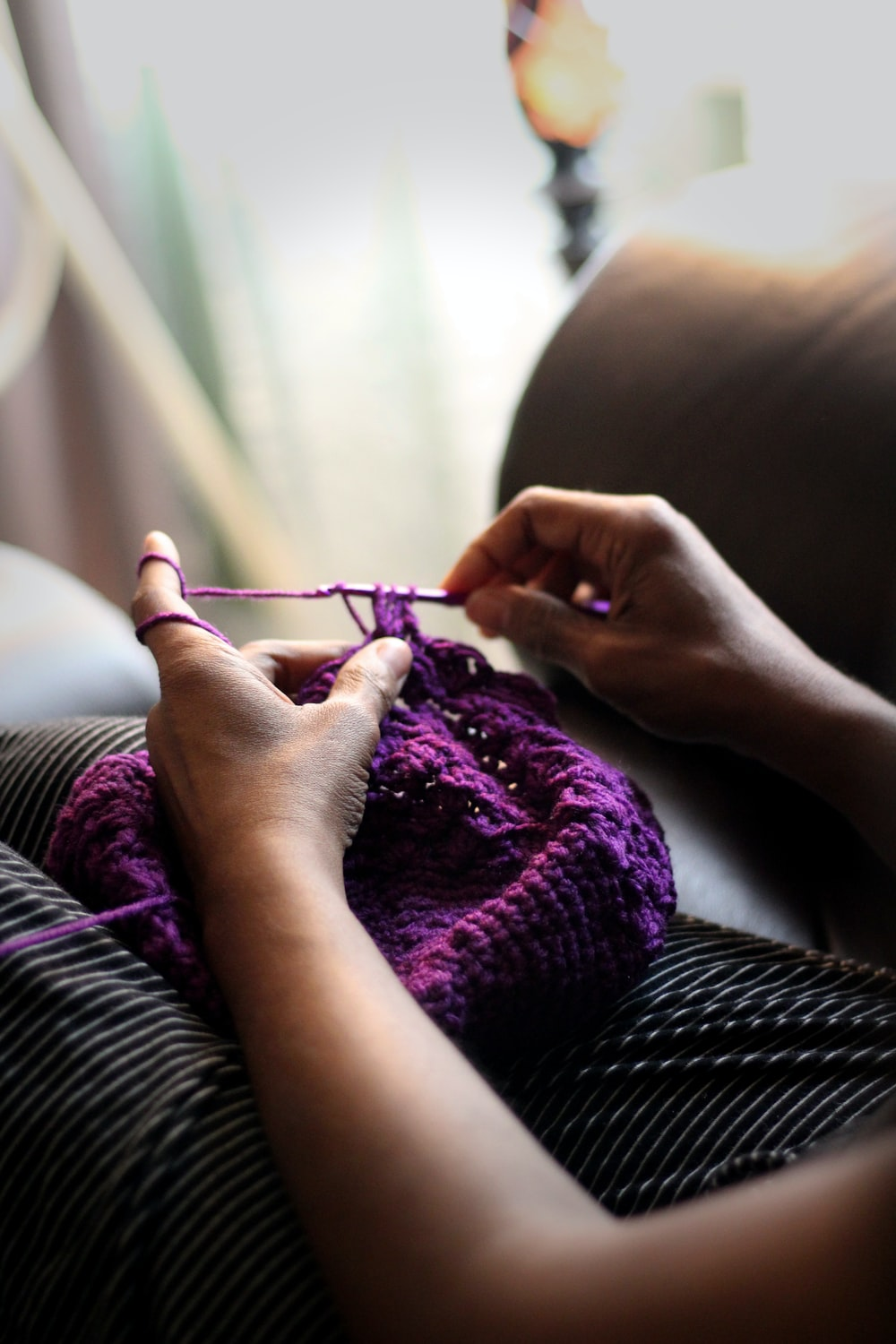 woman sewing purple textile