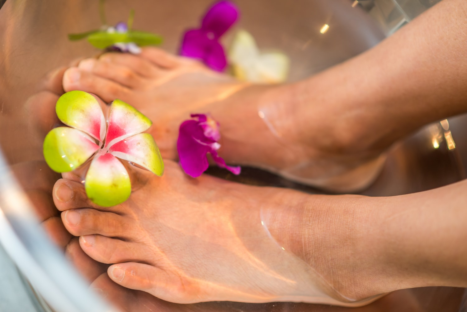 Feet soaking on a water with flowers