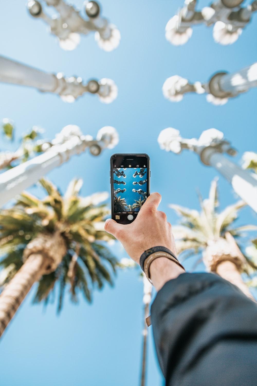 person raising black smartphone