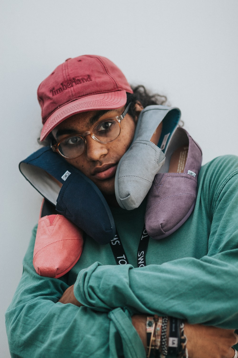person with three assorted-color Toms shoes on his face