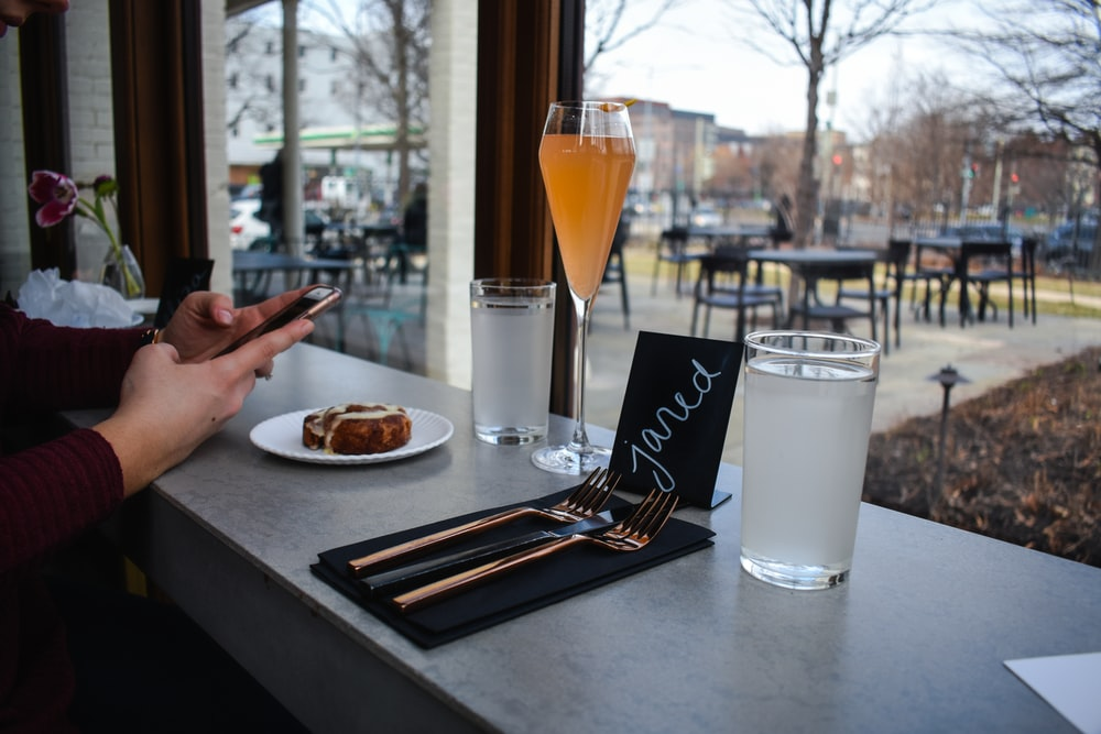 person holding smartphone near long-stem drinking glass