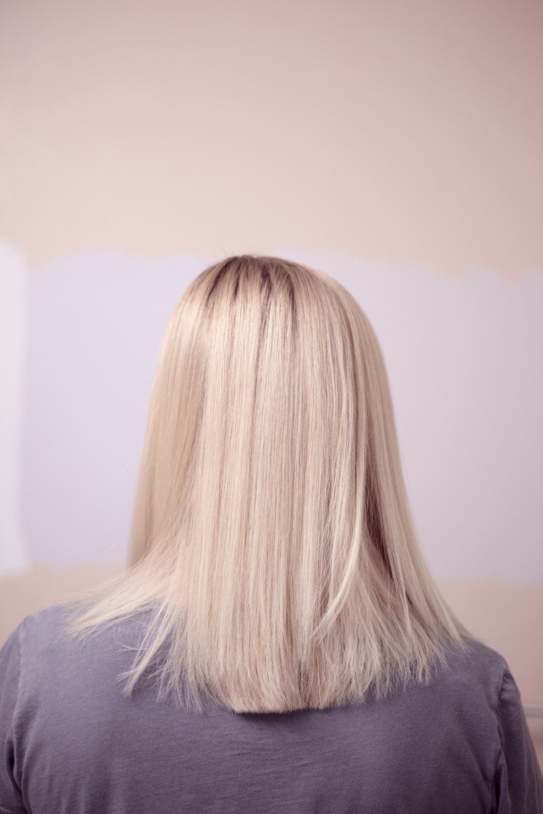 Portrait from behind of a young woman with lightened blonde hair.