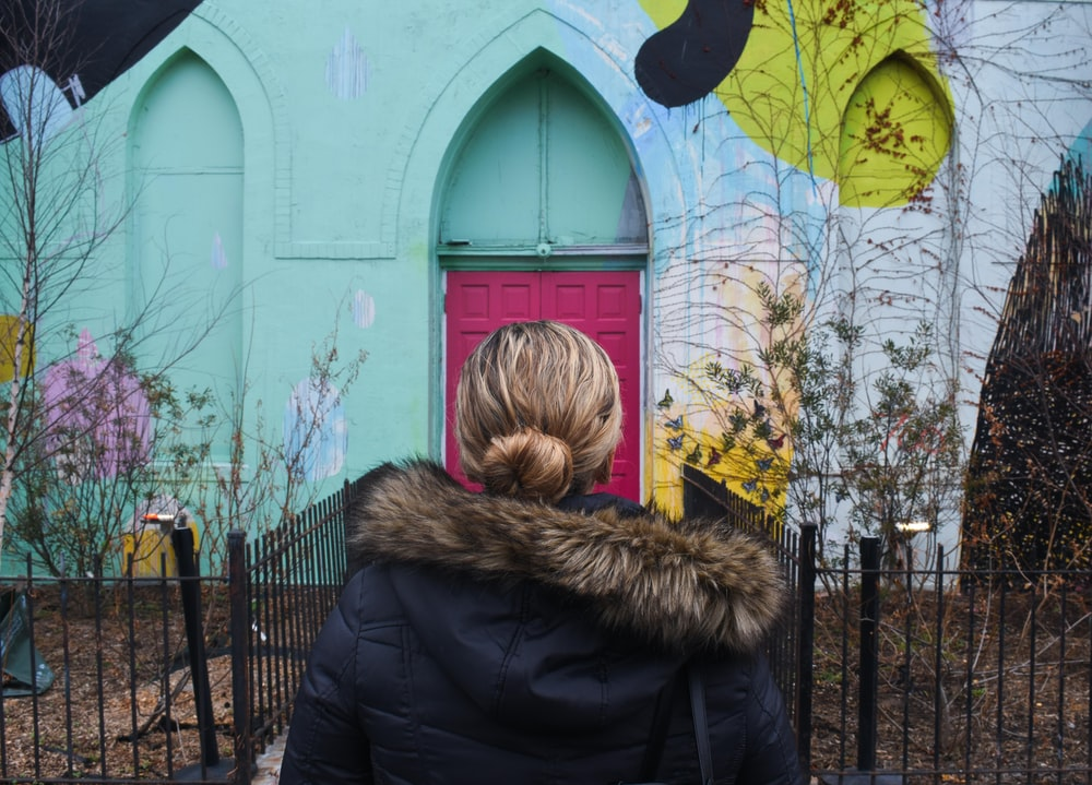 woman wearing parka jacket standing in front of teal house