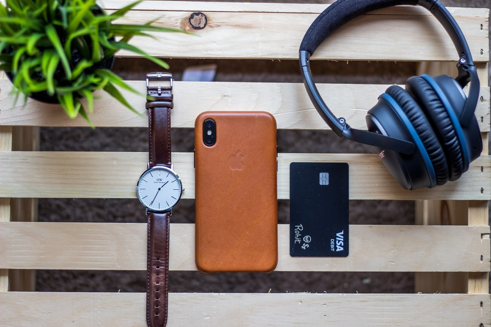 brown iPhone case beside round silver-colored analog watch on brown wooden table