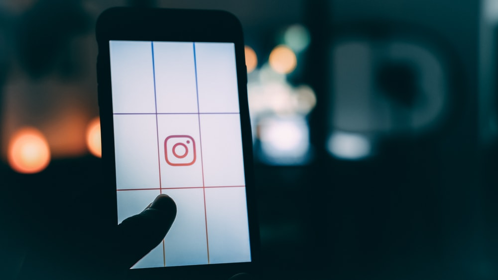 person using smartphone with Instagram logo screengrab bokeh photography