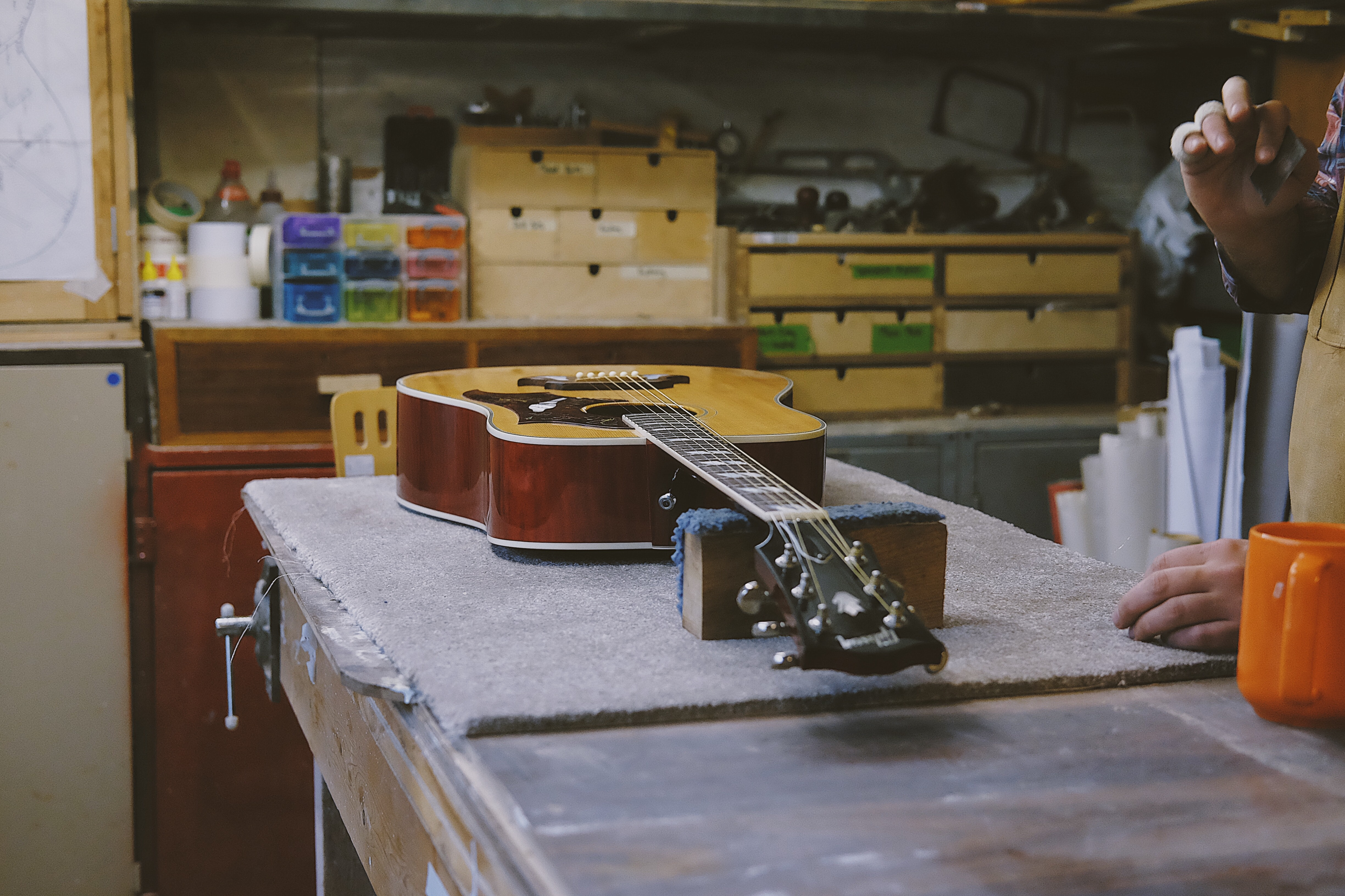 guitar resting on table near person in the kitchen
