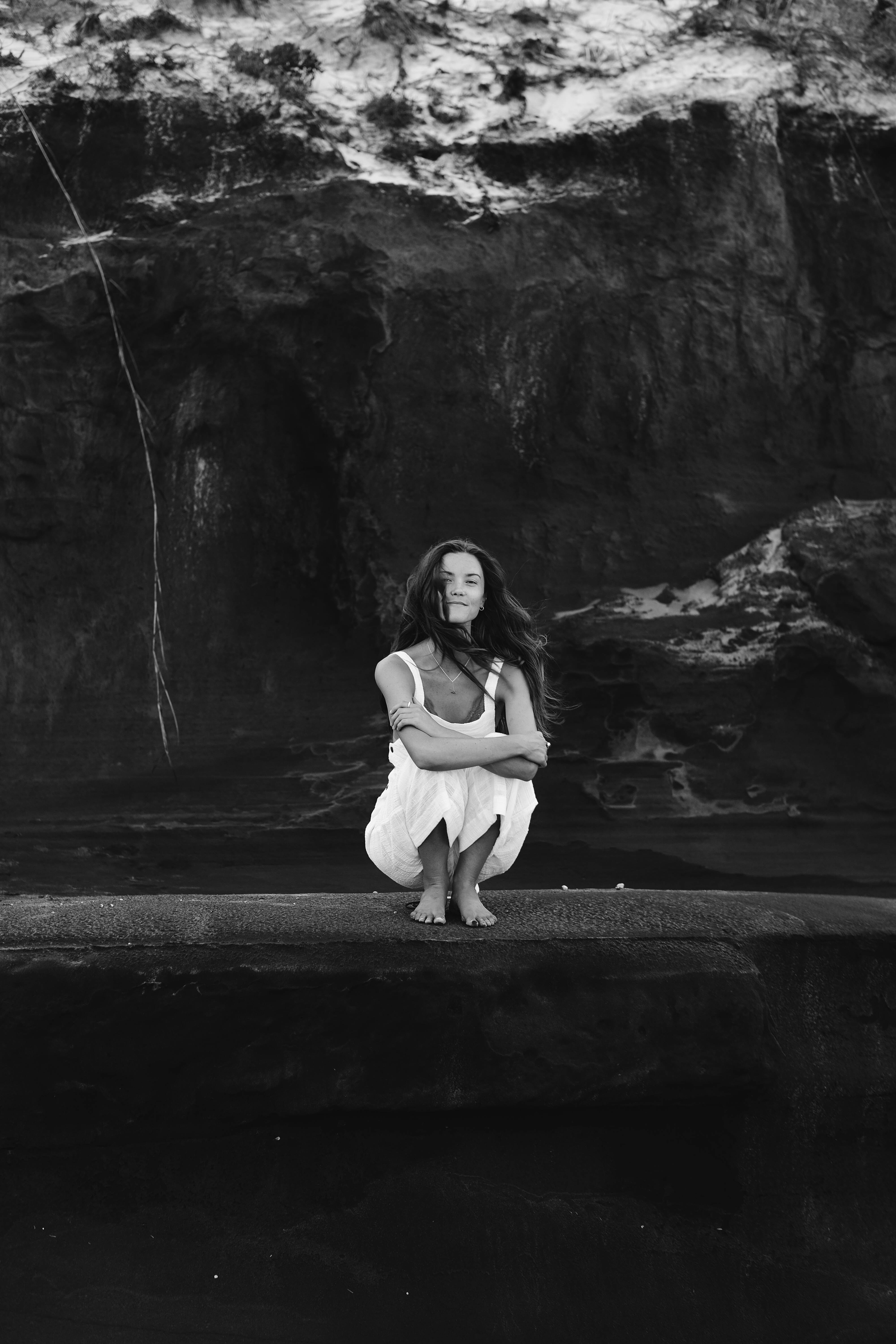 grayscale photo of woman hugging her knee with rock formation background