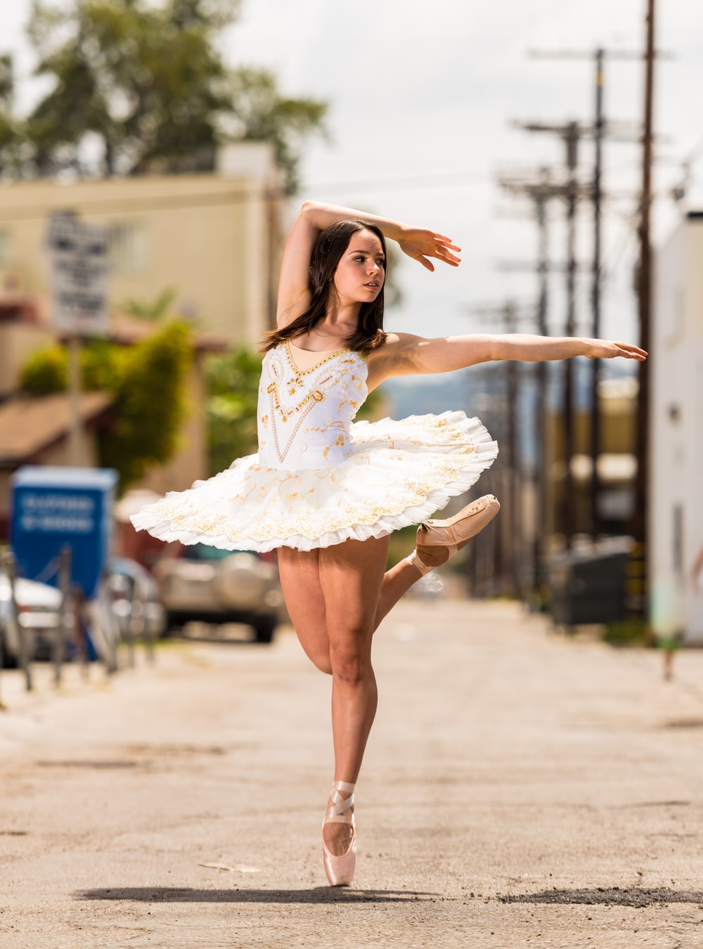 shallow focus photography of woman in white dress dancing