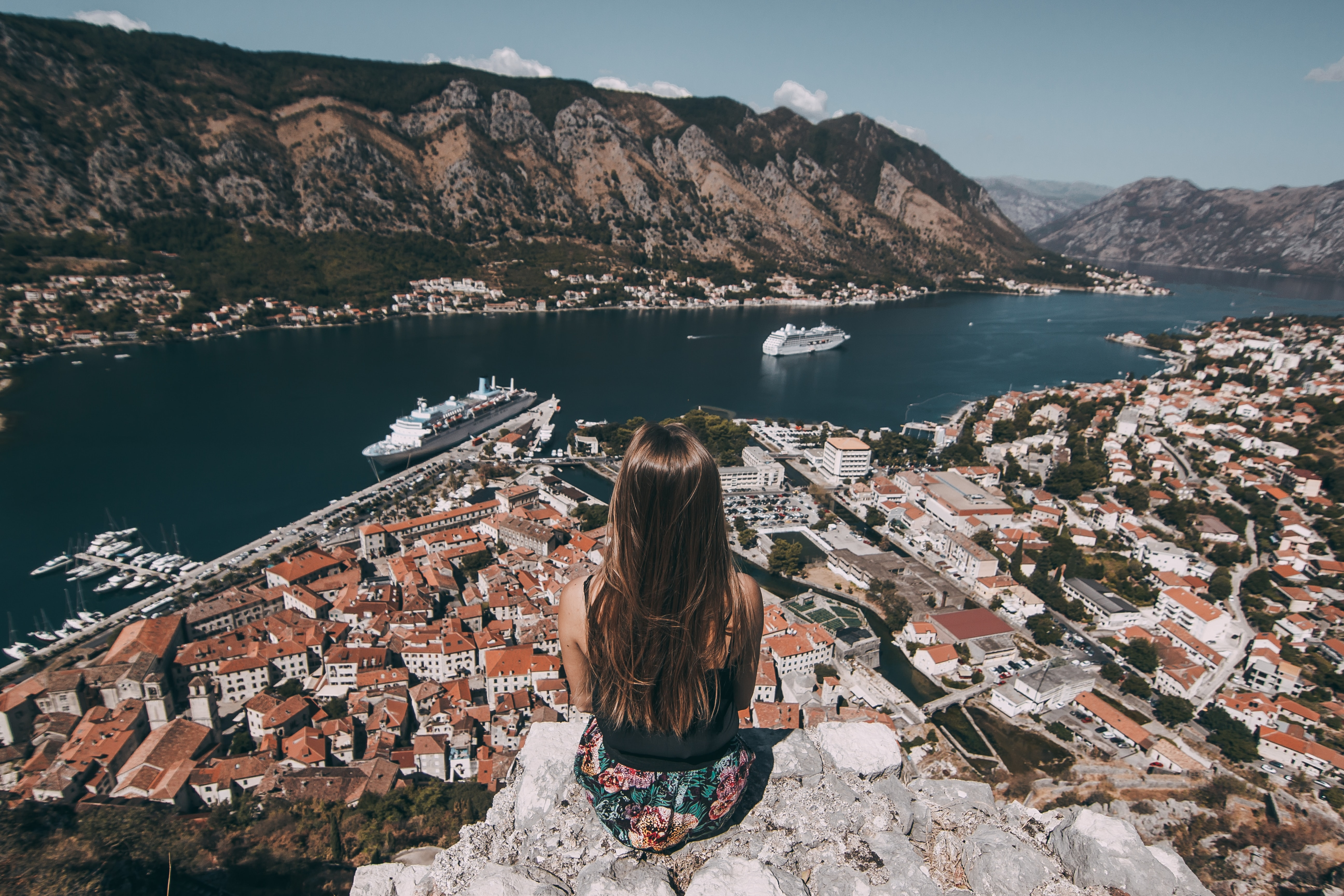 woman sitting on top of cliff facing buildings