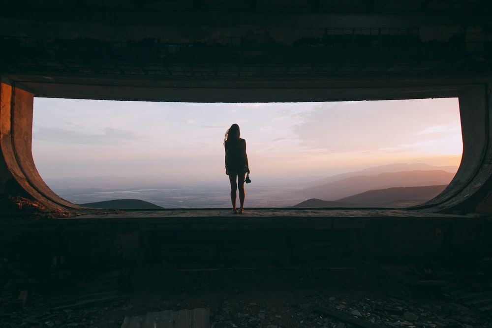 silhouette of woman standing on the edge looking at mountains