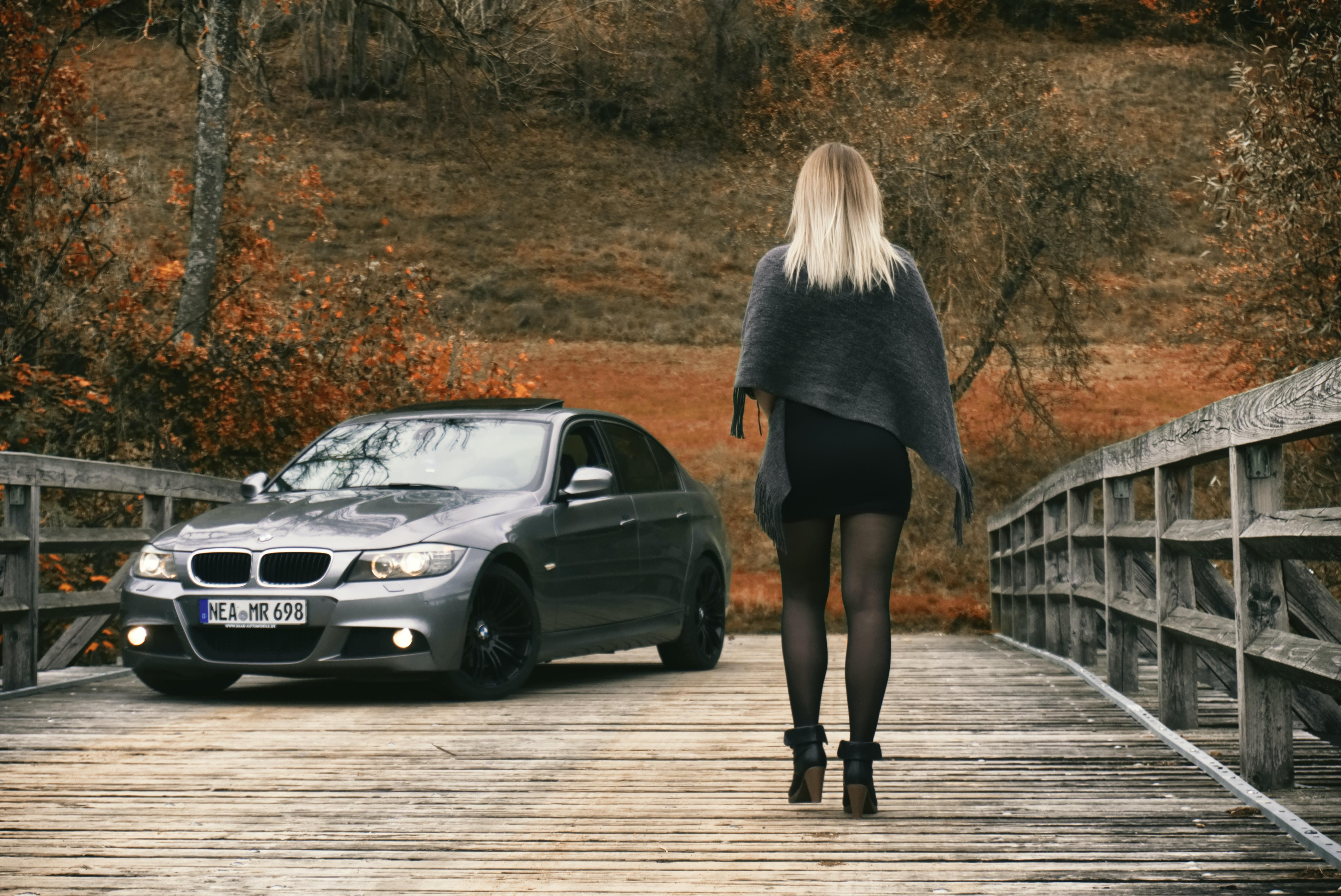 woman walking through gray BMW car at the bridge
