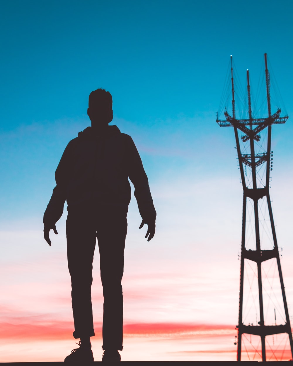 silhouette photography of man standing in front of transmission tower