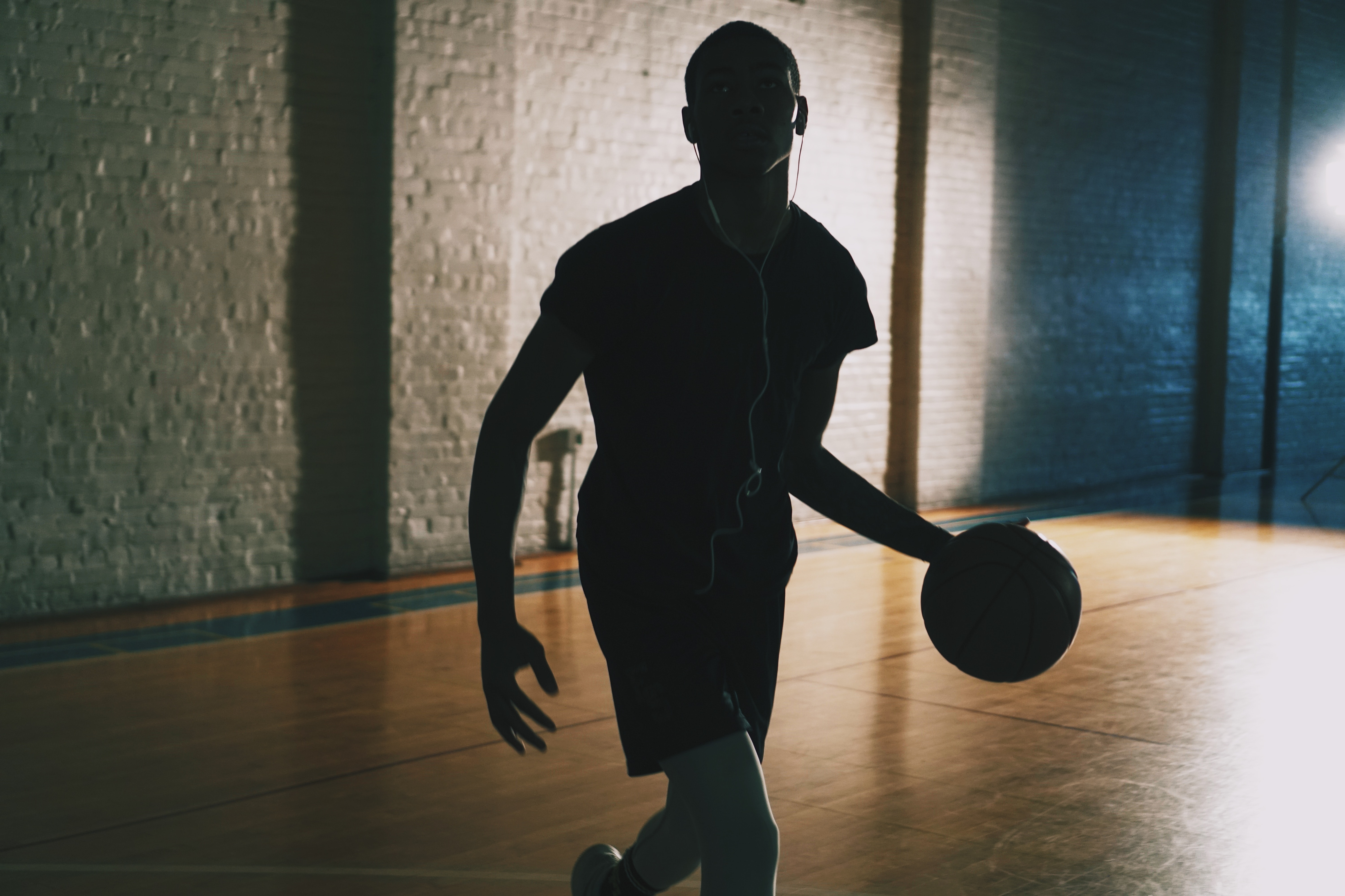 man dribbling ball in closed basketball court