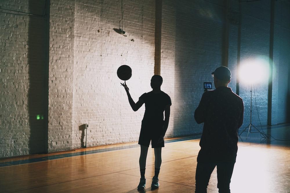 man capturing silhouette photo of man spinning basketball