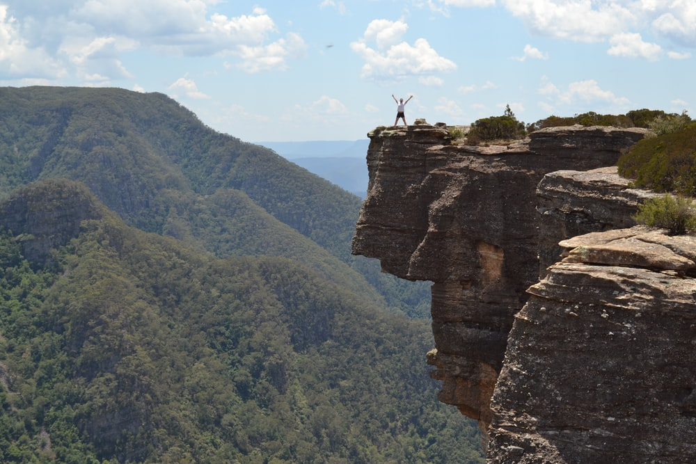person standing on edge of stone cliff with green mountain in the background