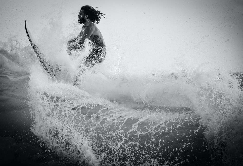 grayscale photography of man surfing
