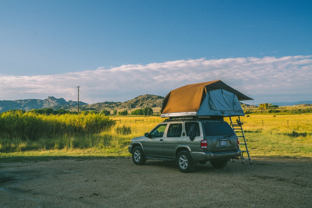 brown SUV parking with tent on top
