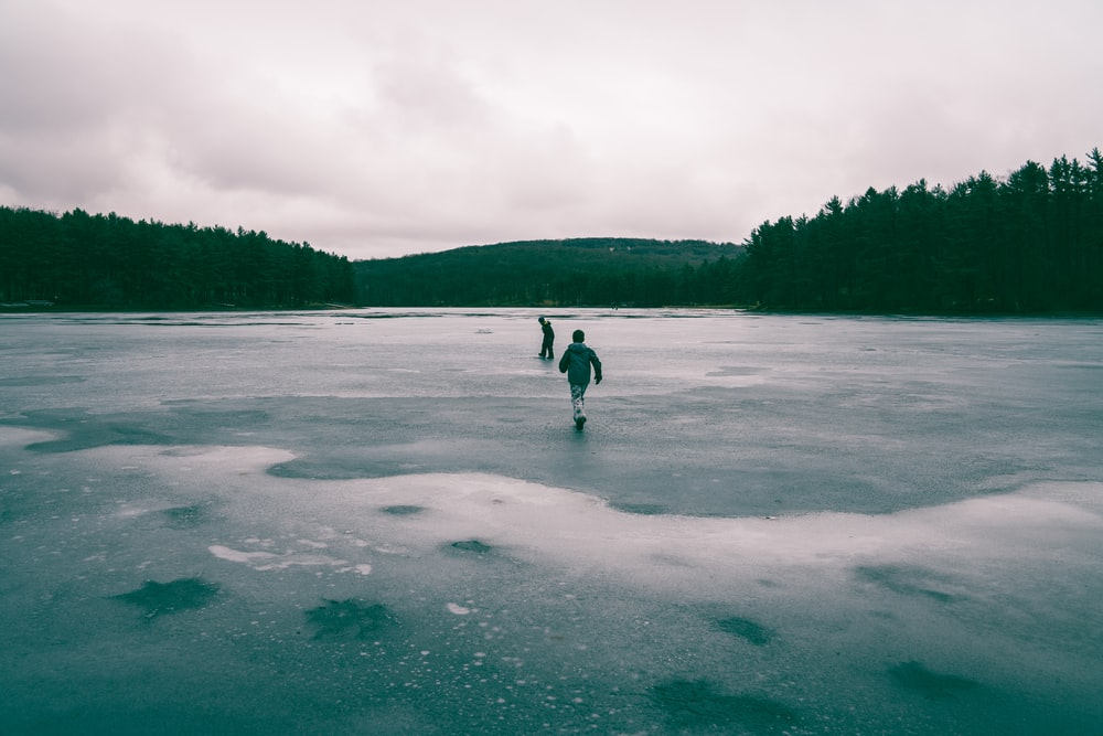 two people in middle of frozen body of water near trees